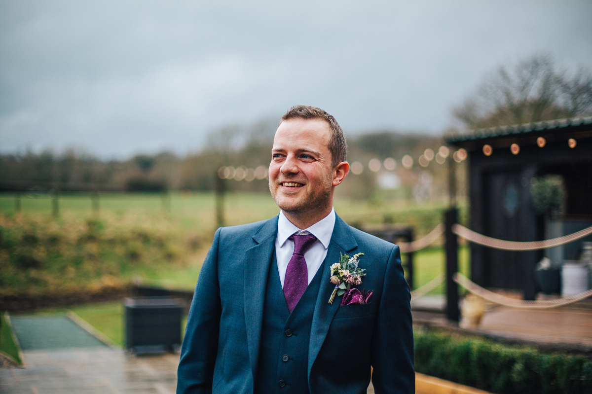 Groom wearing purple tie and navy suit