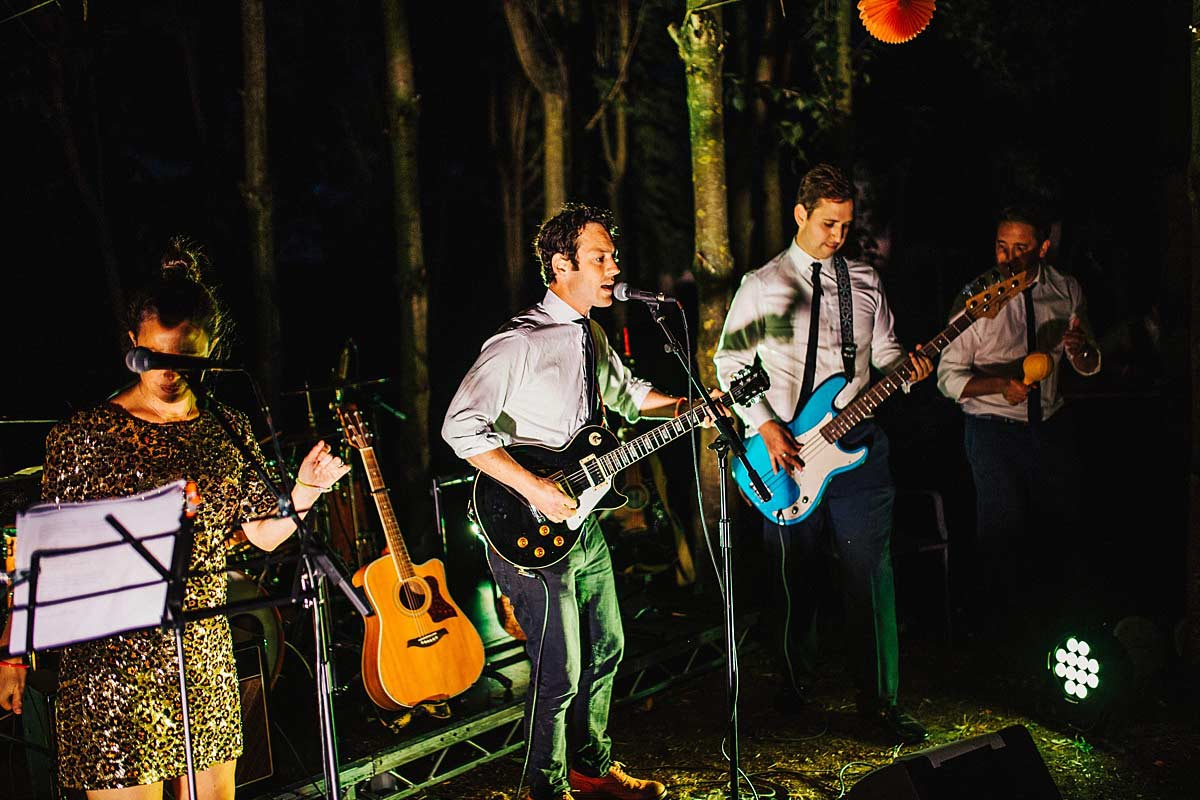 The wedding band playing their set in the woods