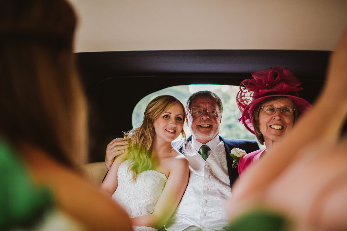 Bride and parents in the wedding car