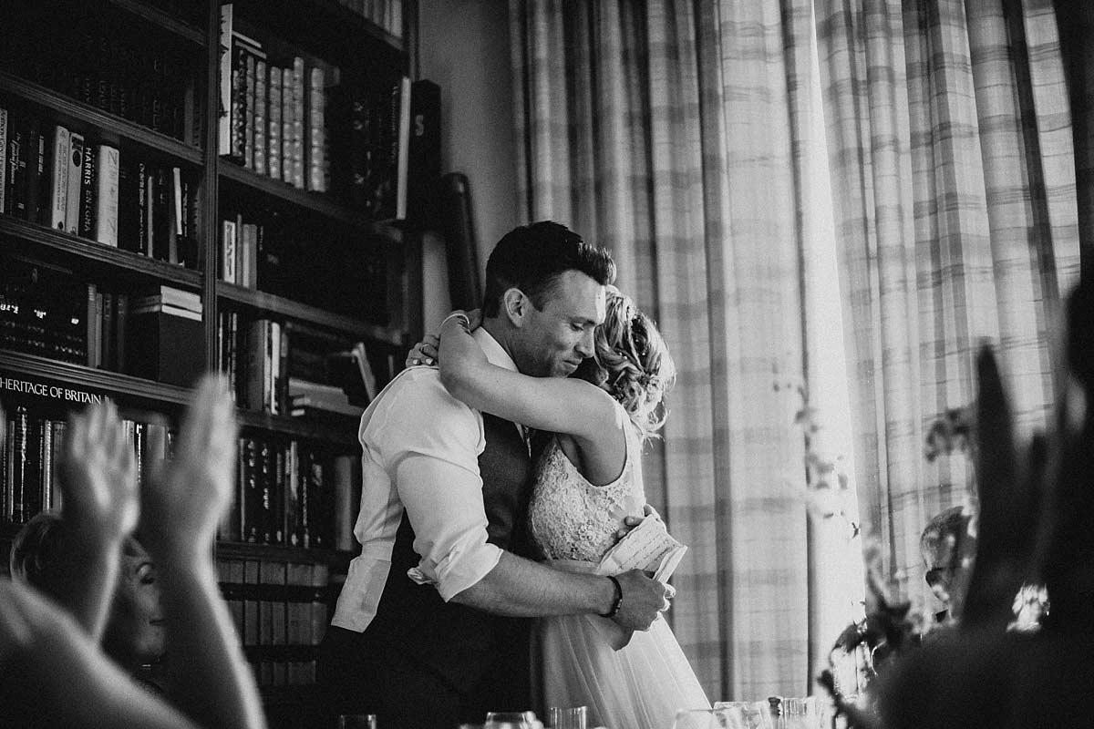 The bride giving the groom a hug