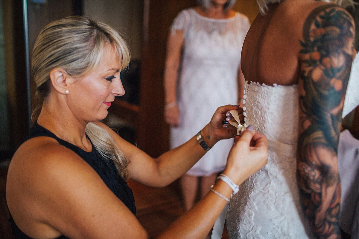 Bride getting into her lace wedding dress