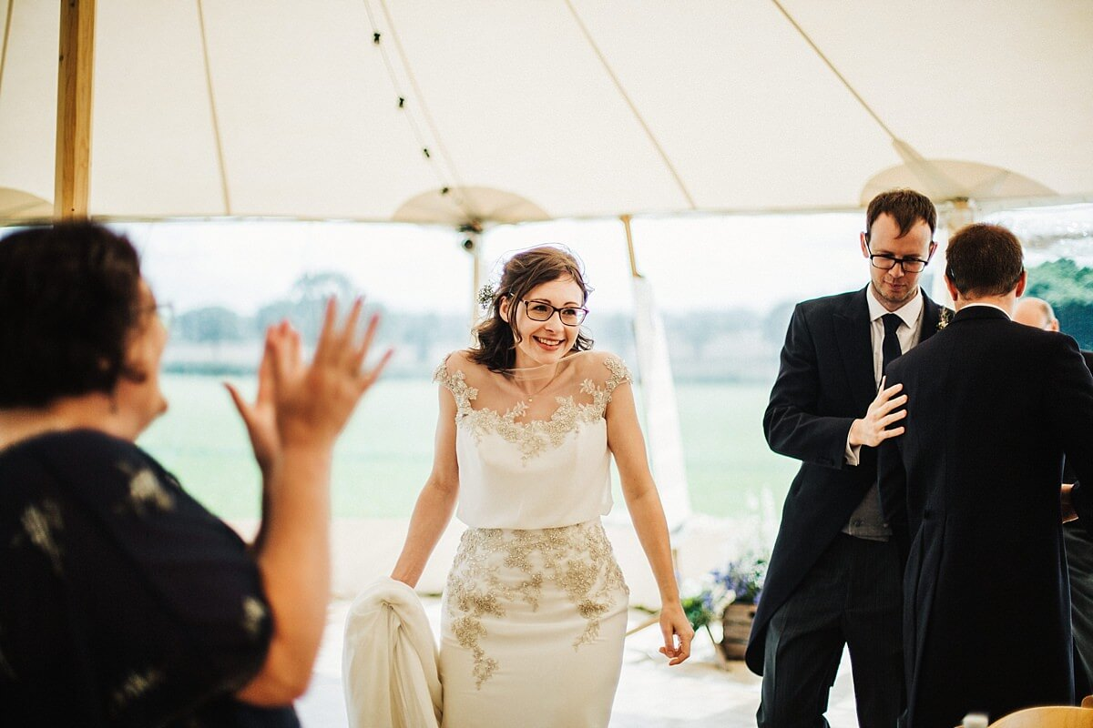 Bride and groom being cheering into the marquee