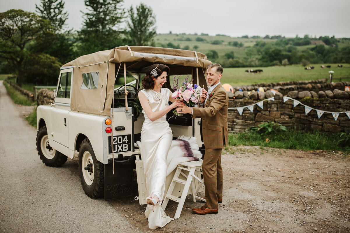 Bride getting out of a white wedding Land Rover