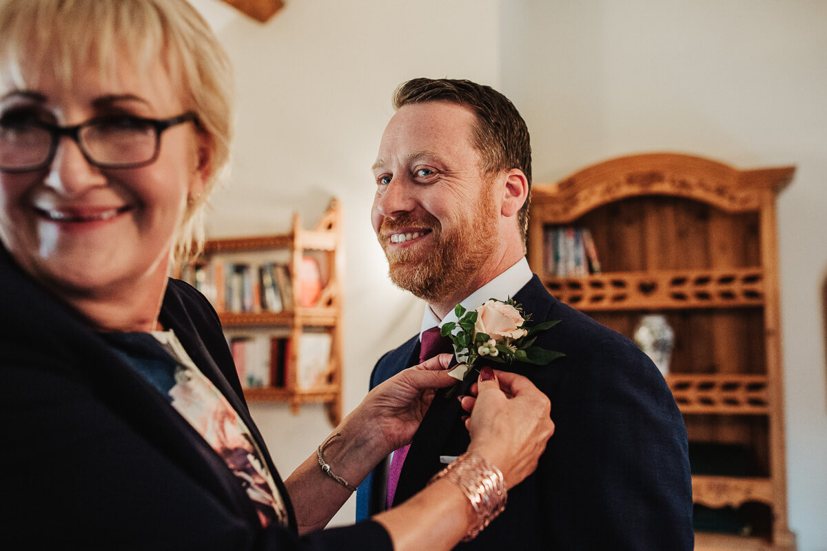 Groom wearing rose button hole