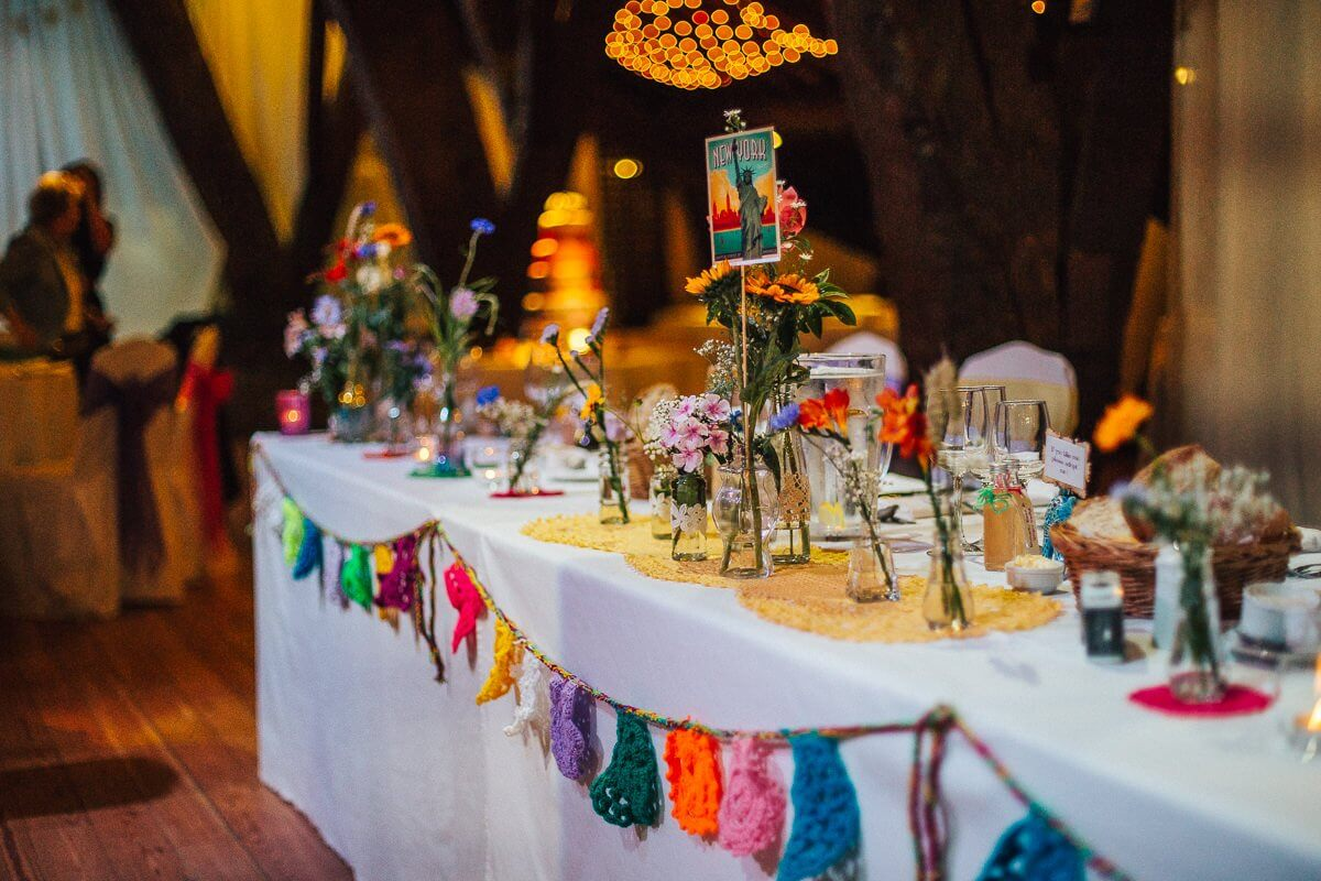 Colourful wedding table decor with flowers and crochet bunting
