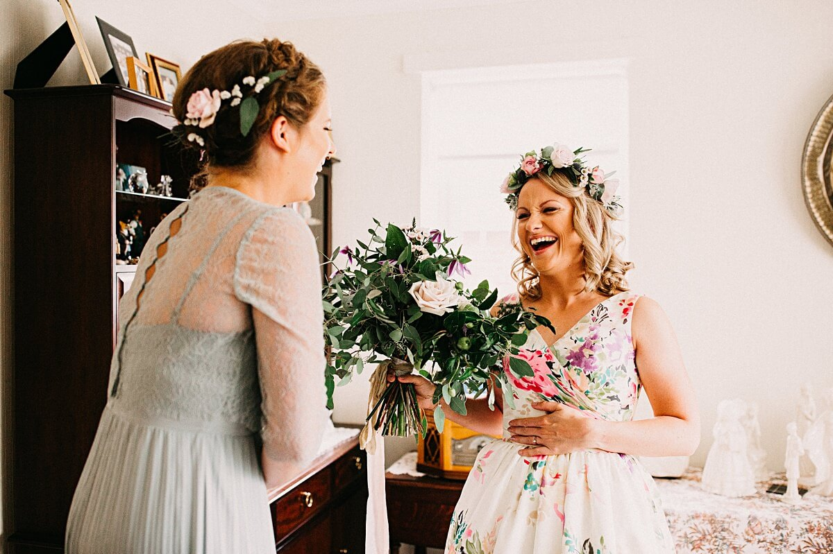 Bride laughing with her bridesmaid