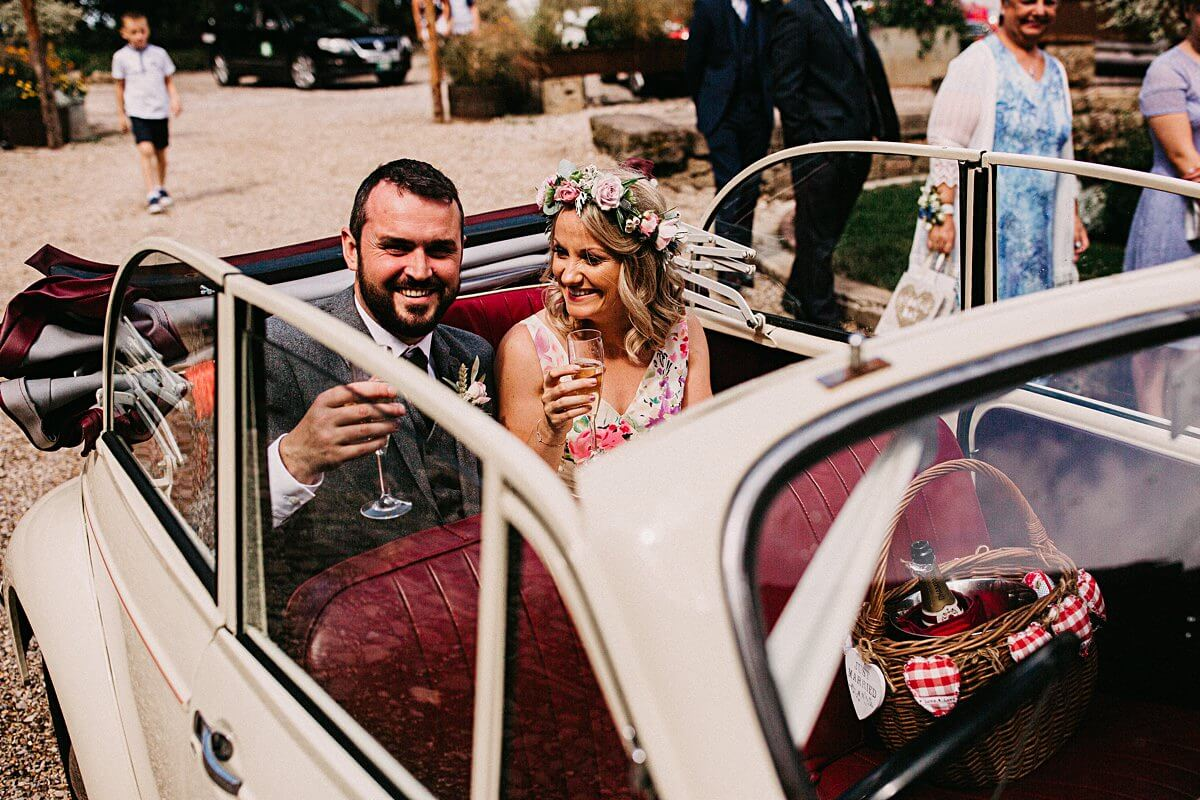Bride and groom inside their morris minor wedding car