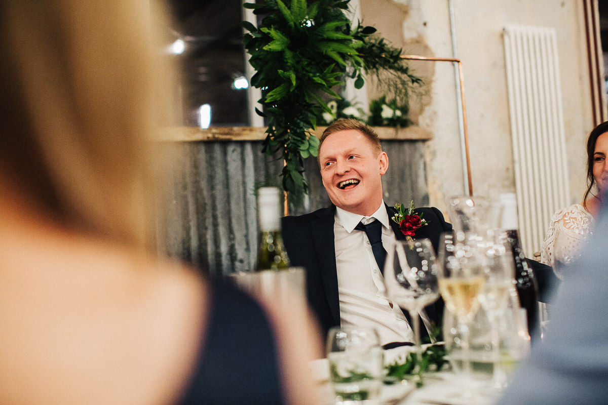 Groom laughing during speeches at Holmes Mill