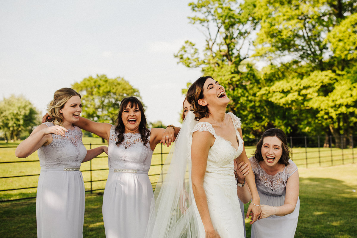 Bride and bridesmaids laughing during portraits
