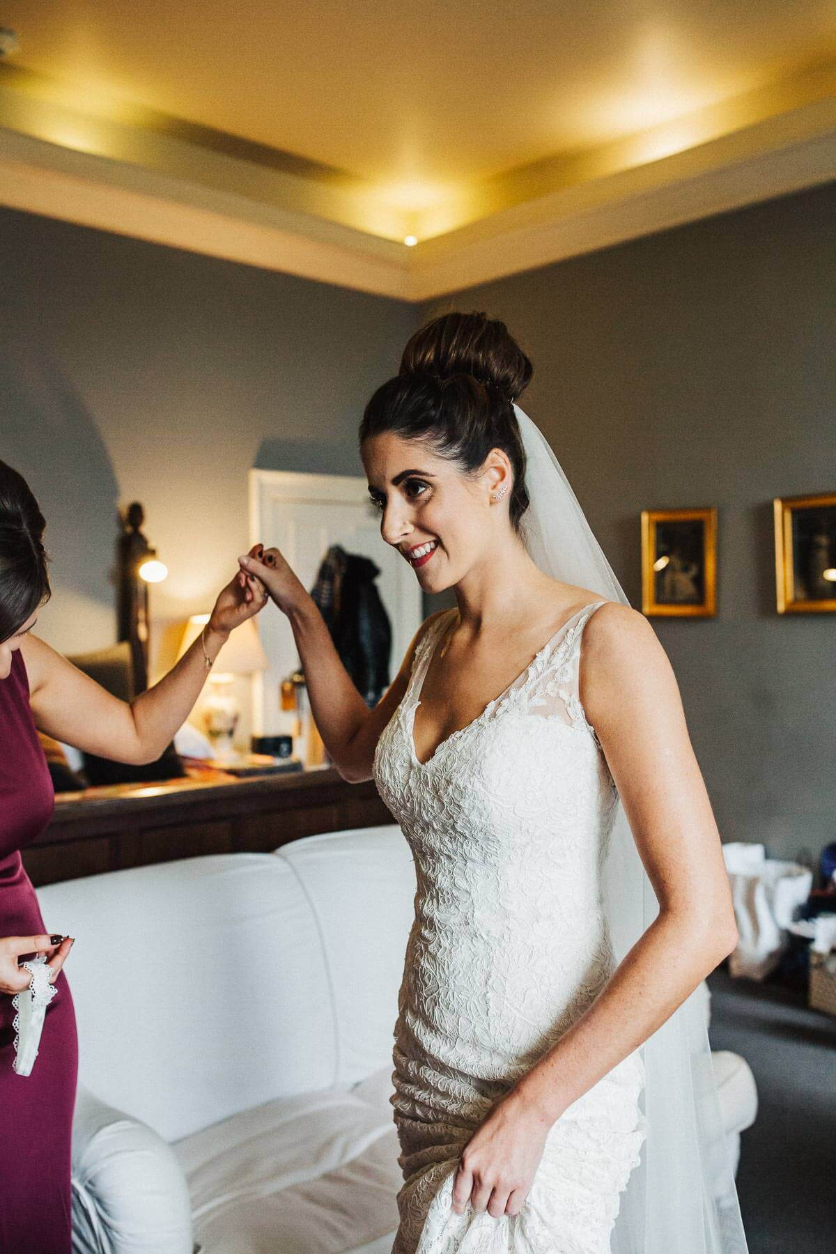 The bride smiling as she's helped into her dress at Askham Hall