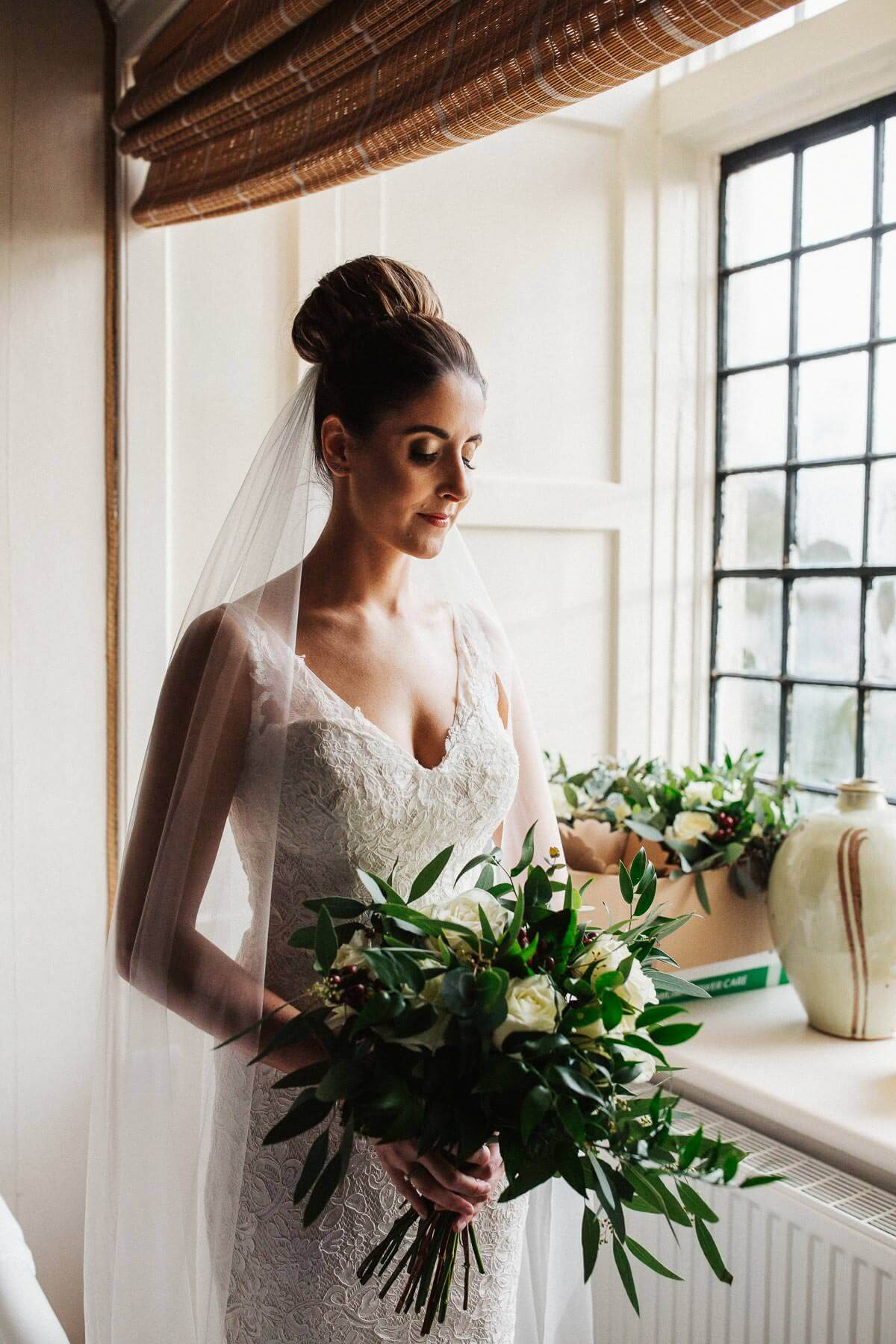 Beautiful bride wearing a lace dress and bun hairstyle