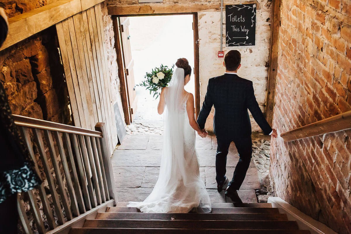 Bride and groom walking through the barn
