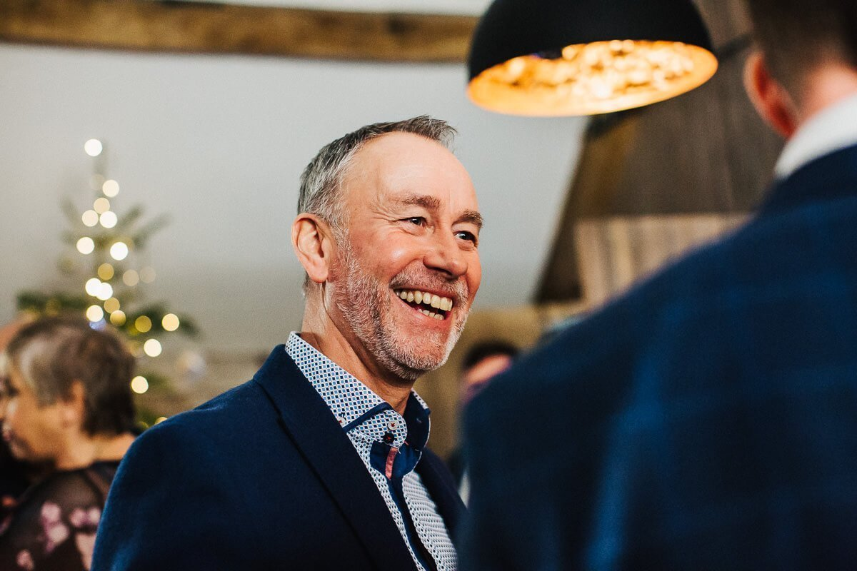 Guest laughing at the winter wedding in Cumbria