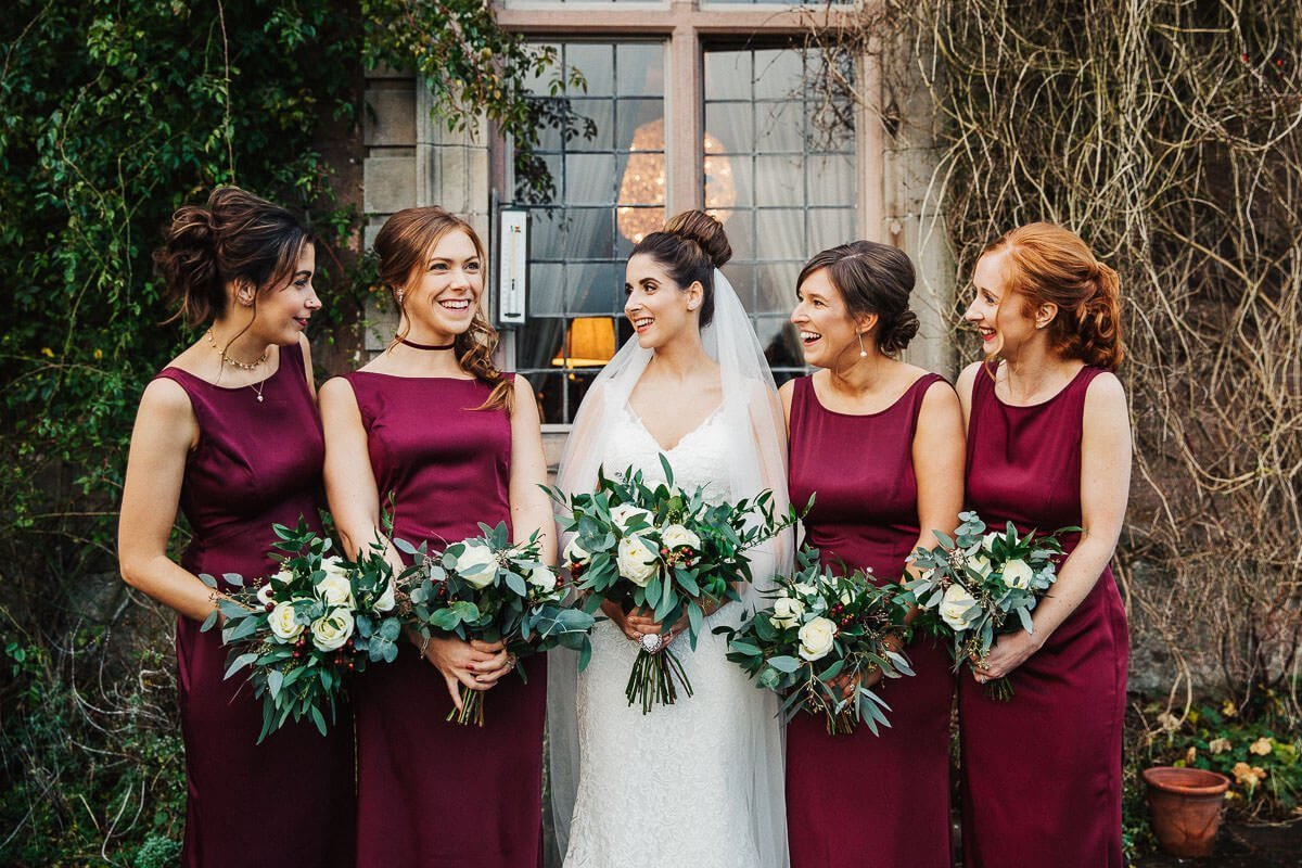 Bridesmaids in burgundy laughing with the bride