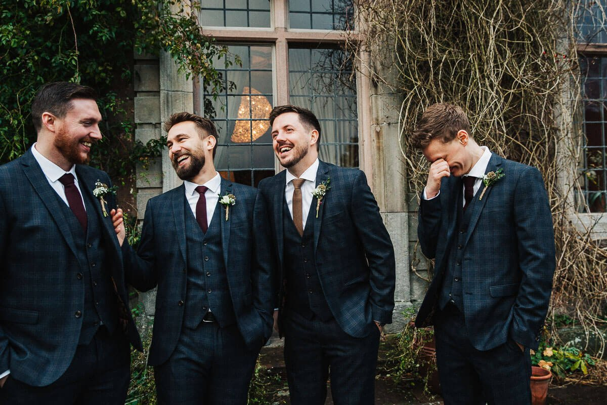 Ushers and groom with blue checked suits and buttonholes