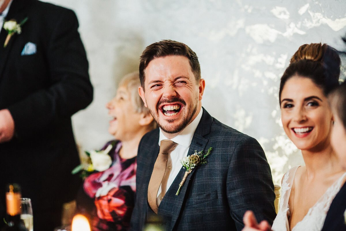 The groom laughing at the wedding speech