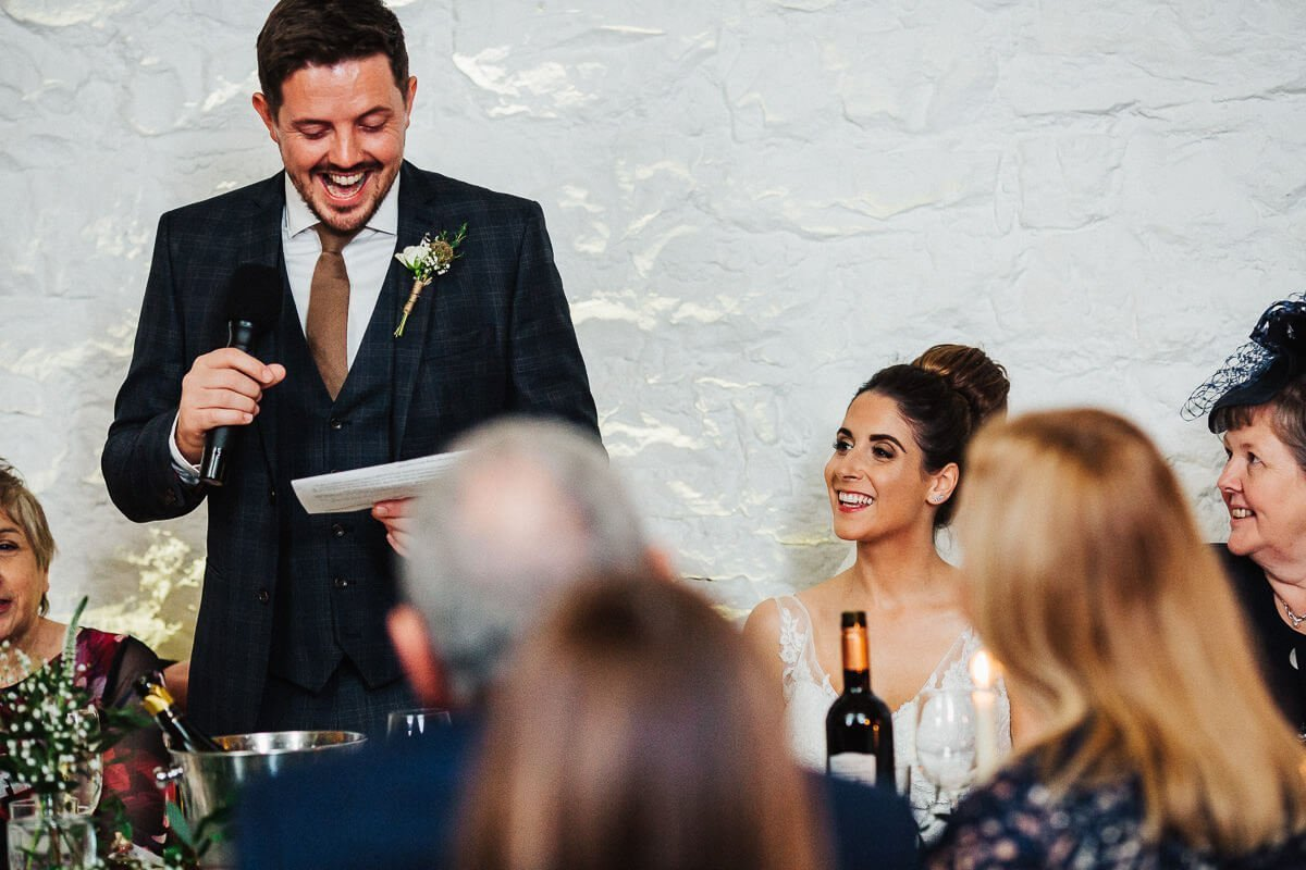 Bride laughing during the groom's speech