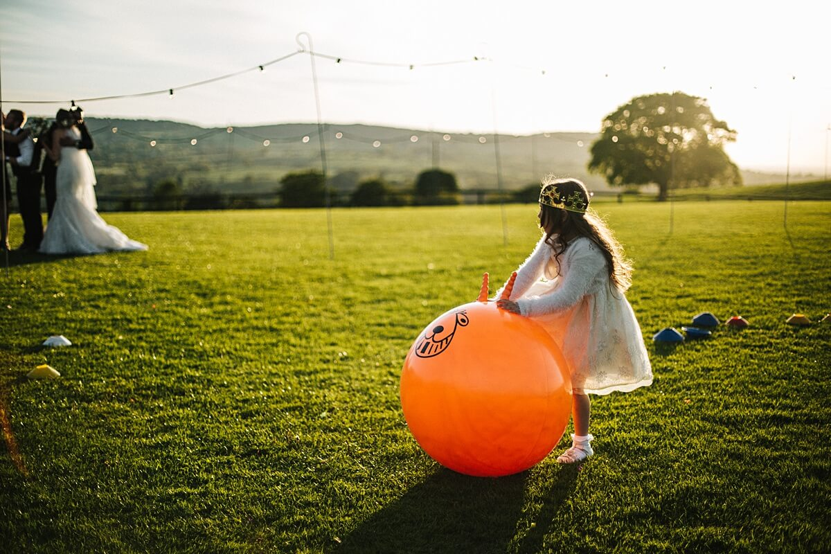 Children playing on space hoppers at the wedding
