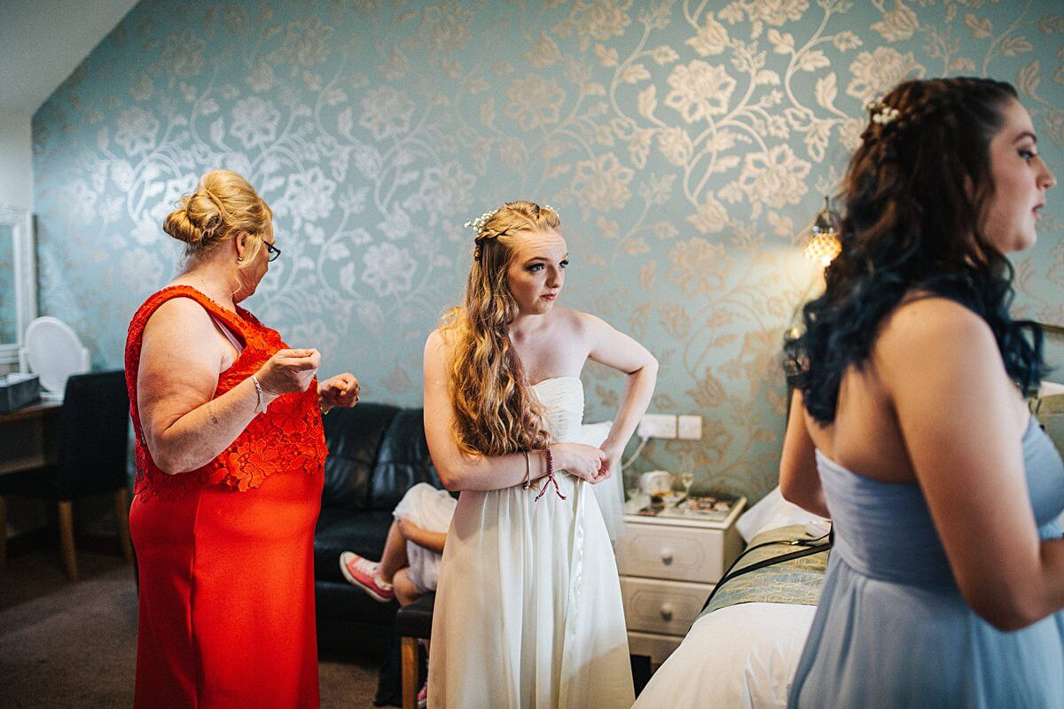 Bridesmaids getting into their dresses