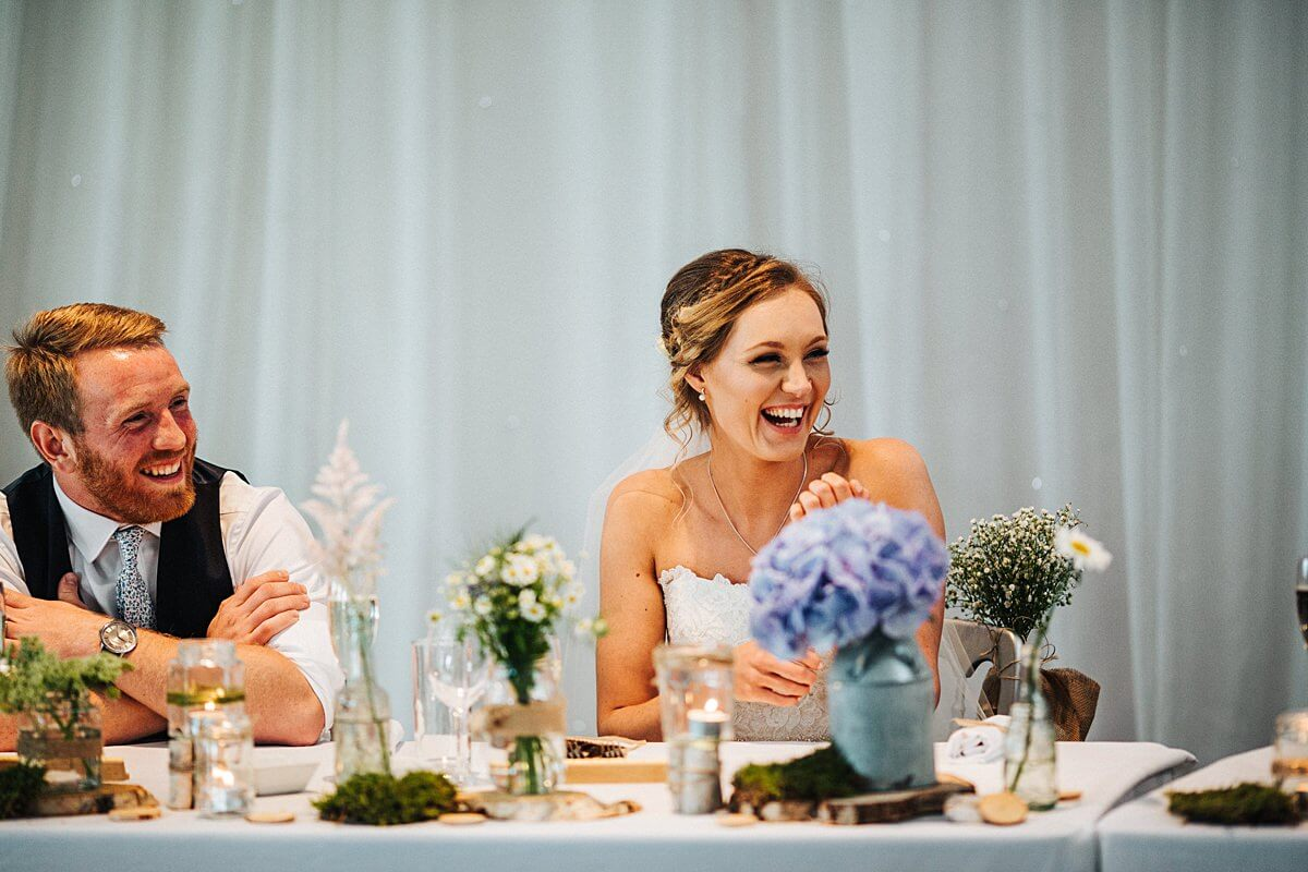 Bride and groom laughing at the Best Man's speech