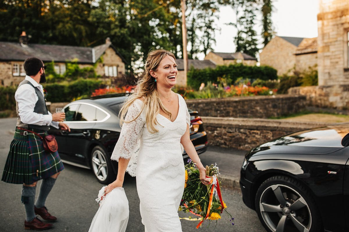 Boho bride walking with colourful flowers