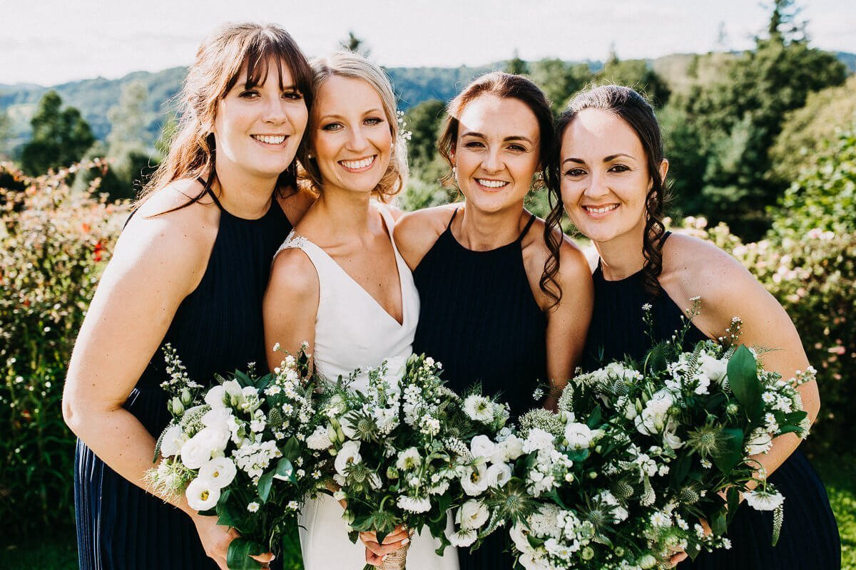 Bride and her bridesmaids with white bouquets