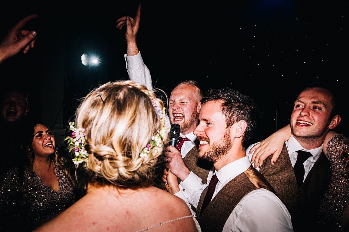 The groom singing on the dancefloor