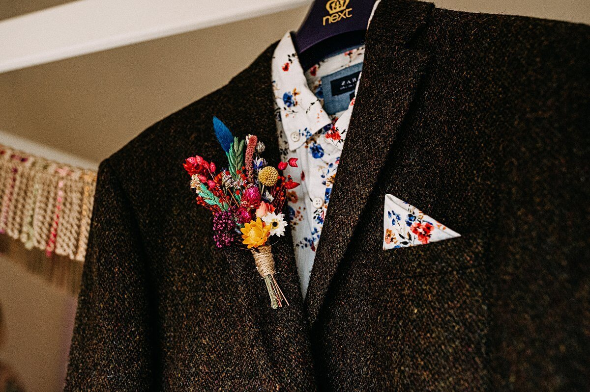 Groom's brown tweed suit and colourful buttonhole