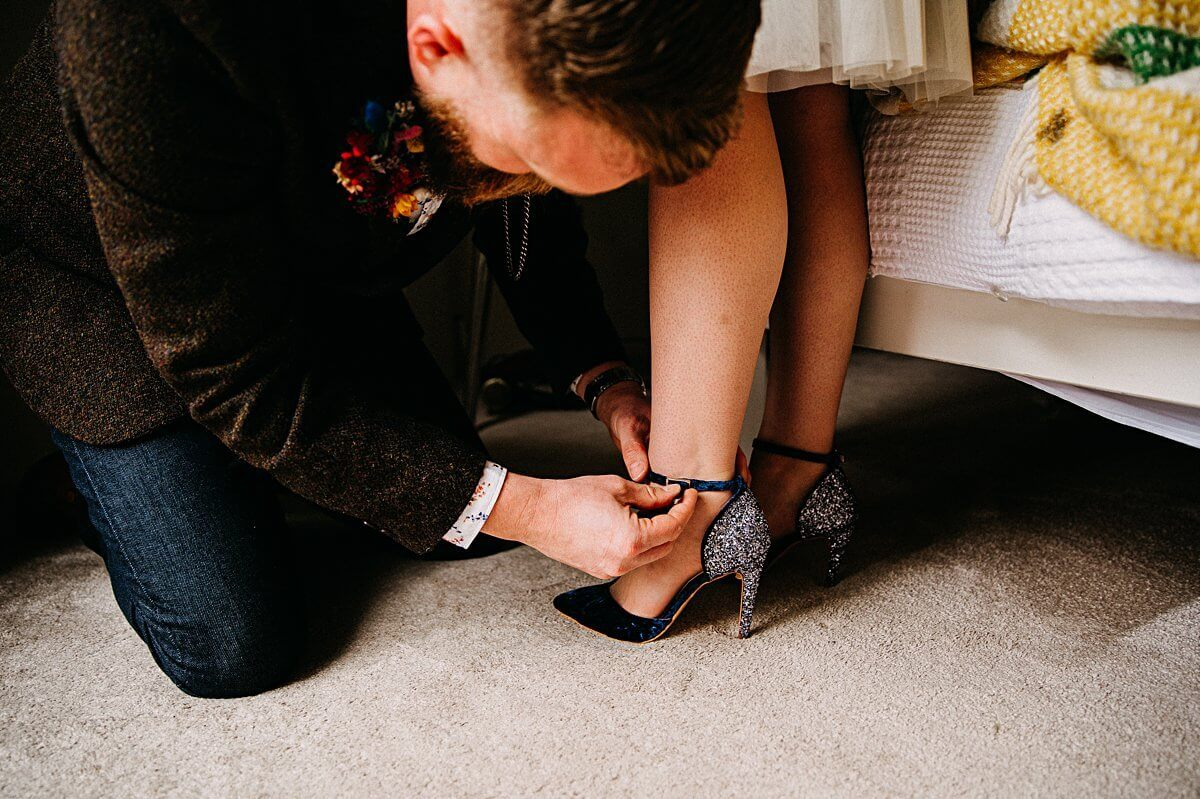 The groom putting the bride's shoes on
