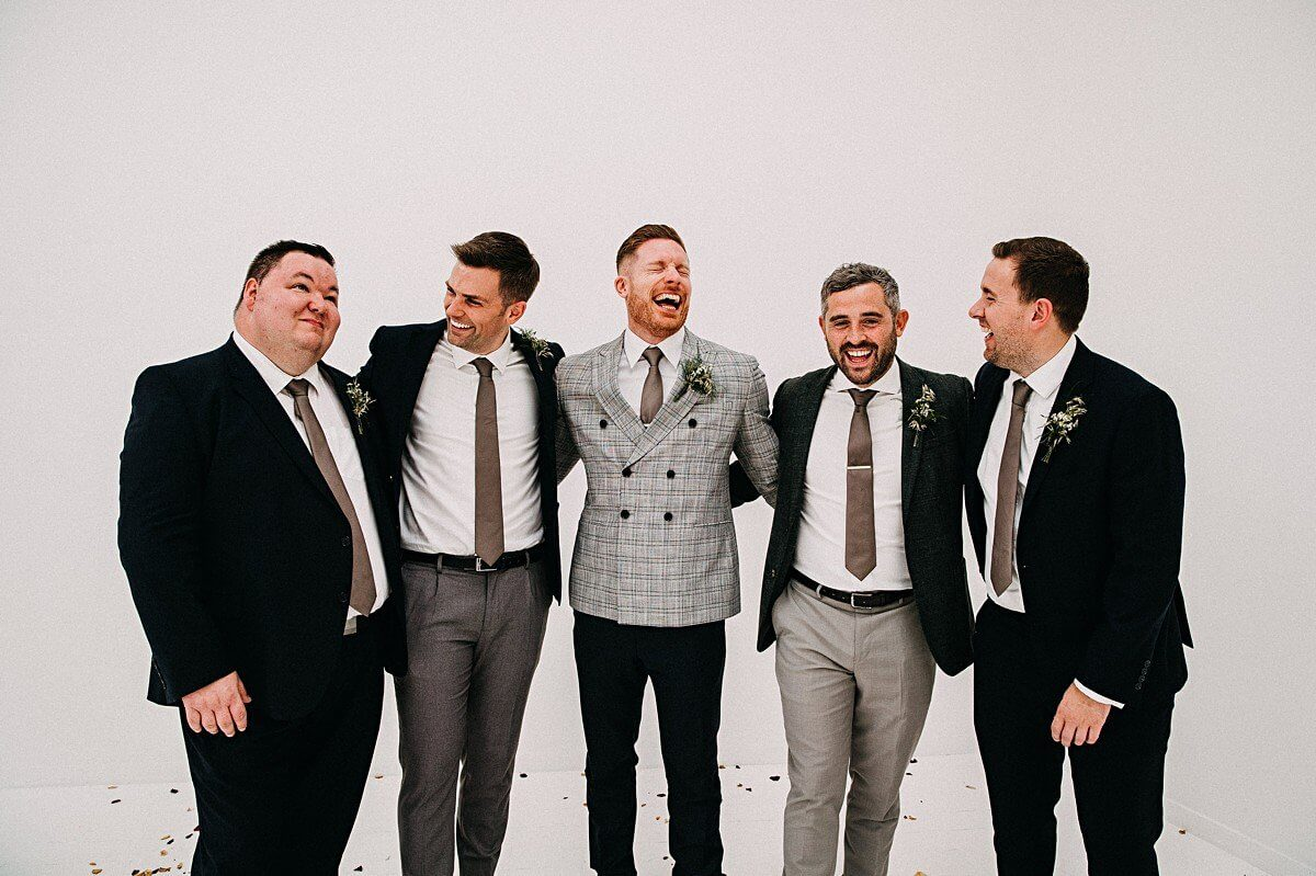 Groom and ushers wearing grey and black suits