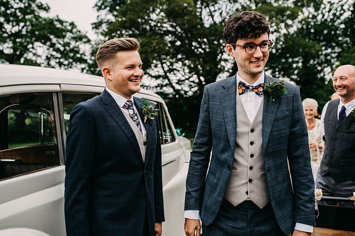 Two grooms wearing blue and grey suits