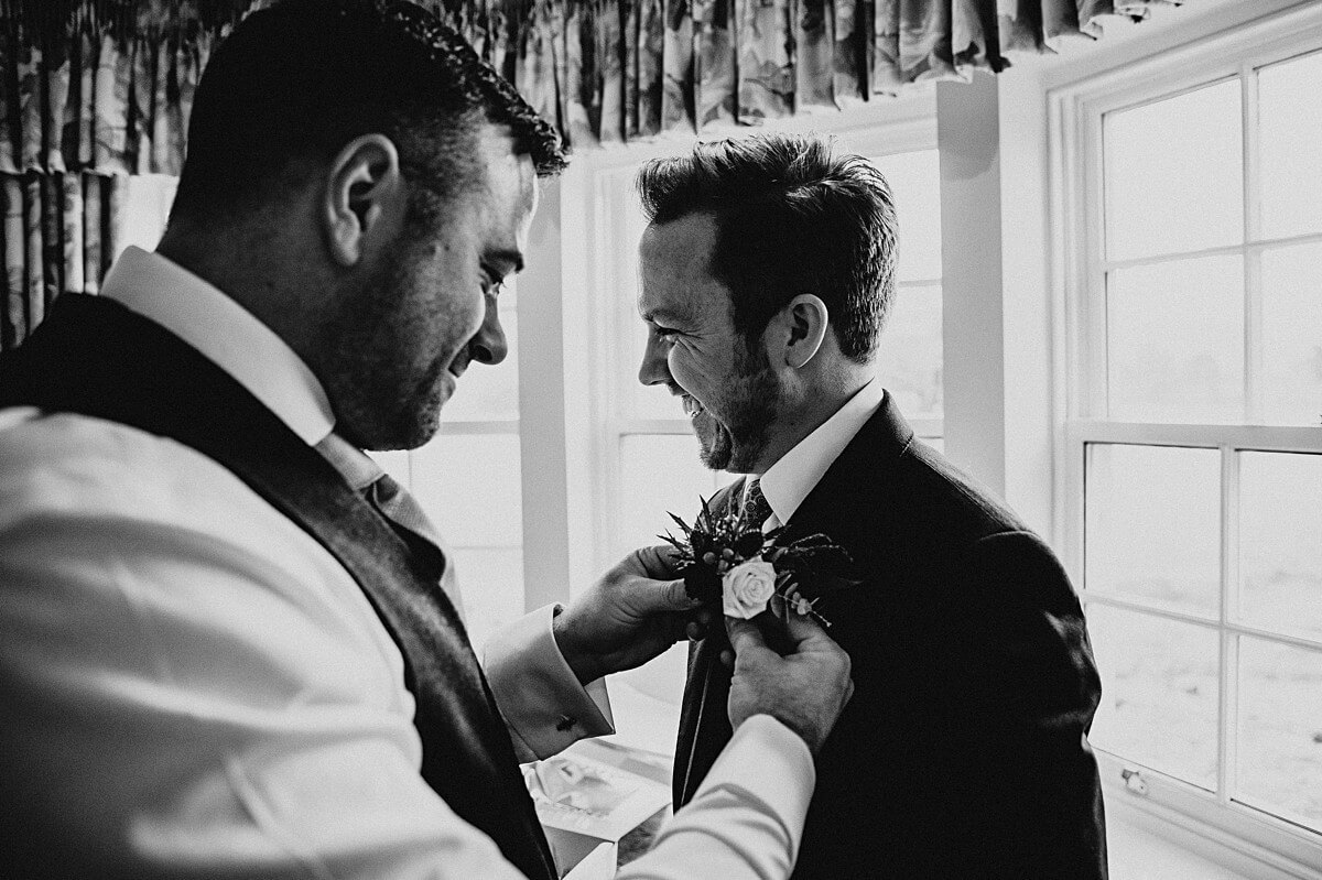 Groom and best man getting into their suits