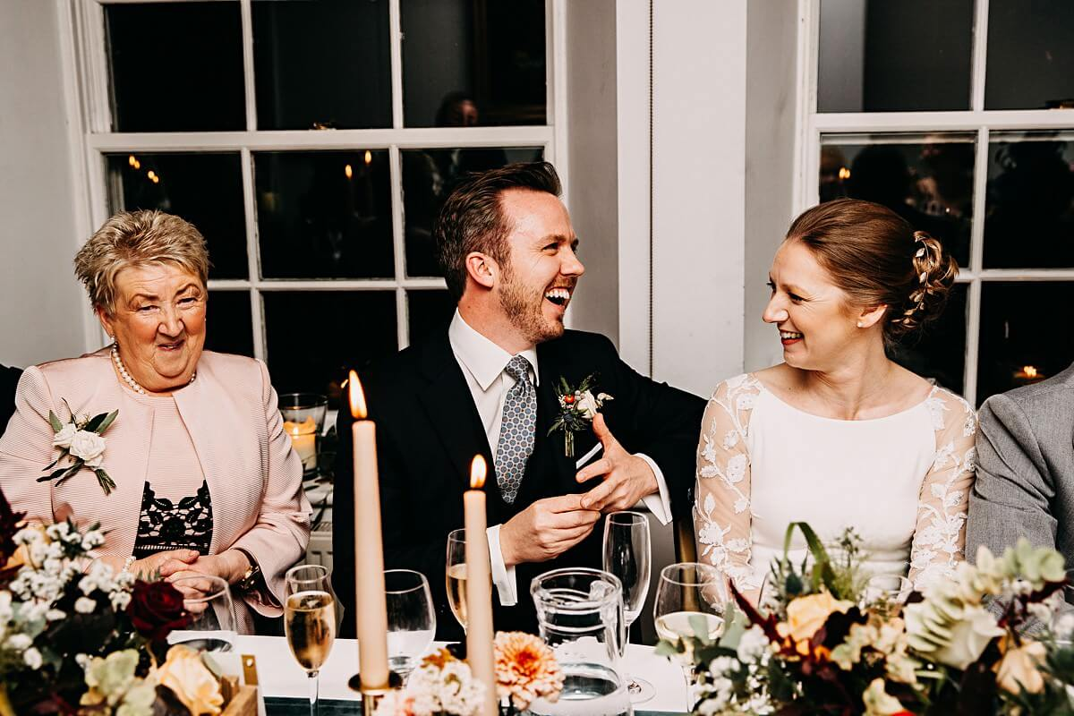 Groom laughing at the best man speech