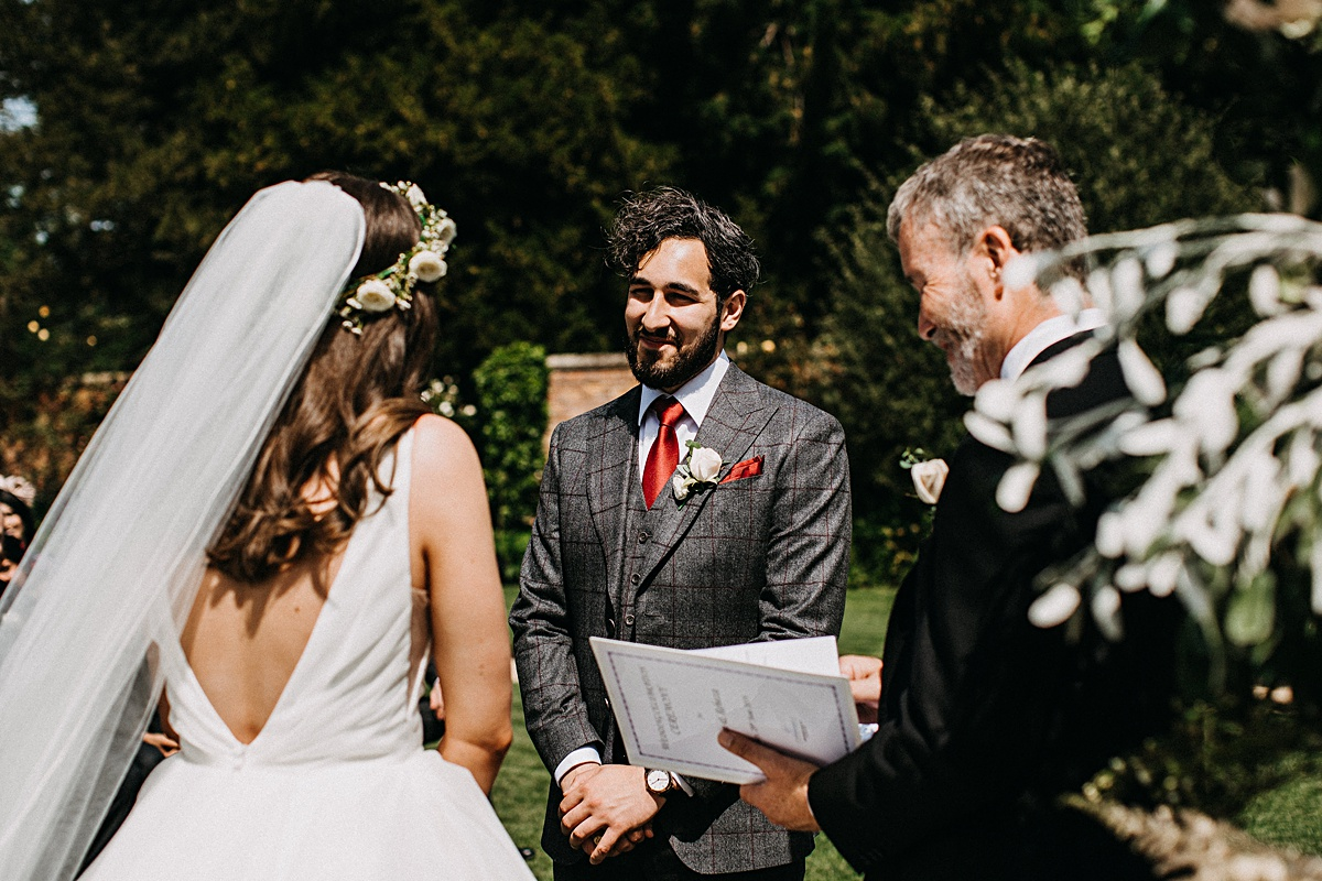 Groom smiling during the wedding vows