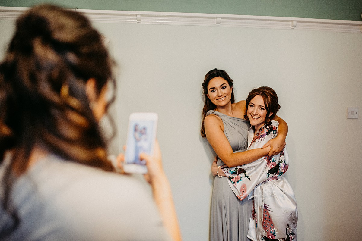 Bride hugging her bridesmaid for a photo