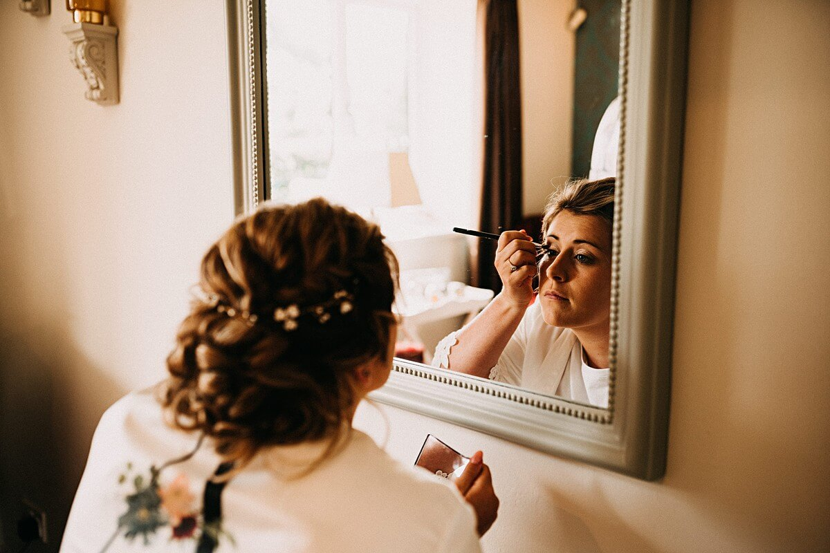 Bride doing her makeup on her wedding day