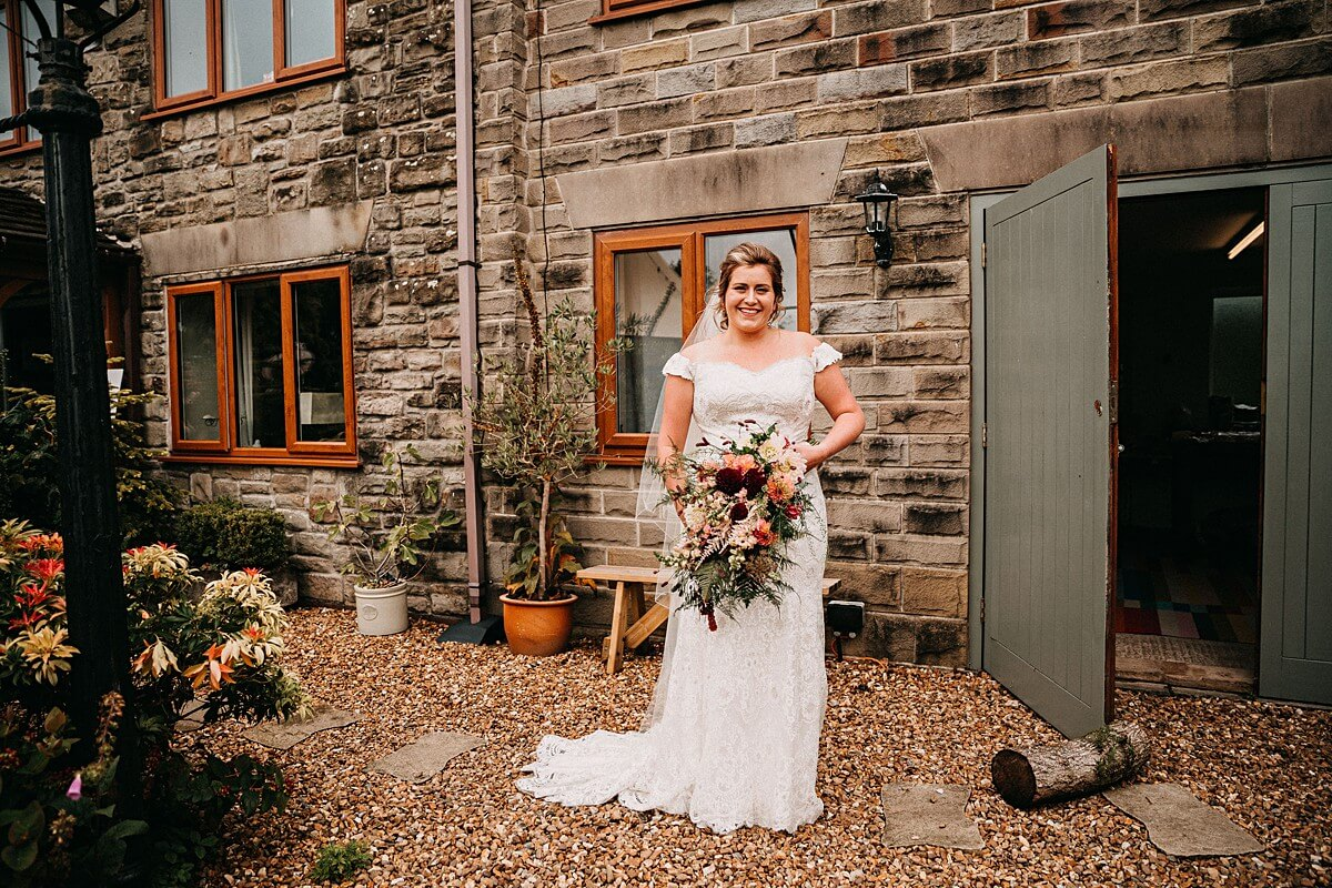 Portrait of the bride in her lace dress holding a colourful bouquet