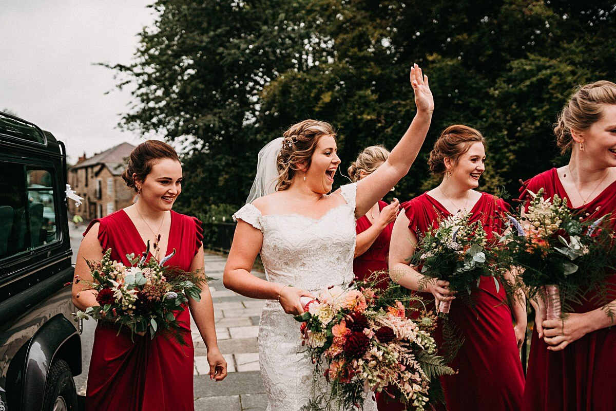 Bride waving at guests holding a colourful bouquet