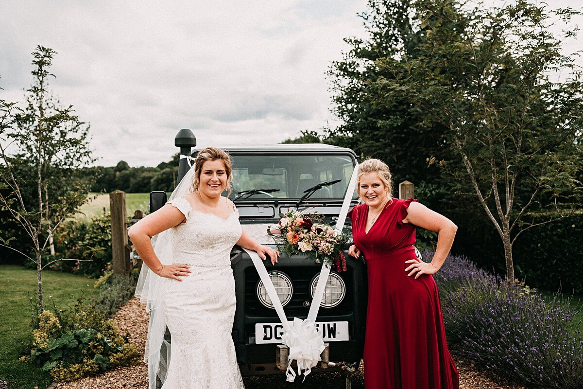 Bride and bridesmaid with the land rover wedding car
