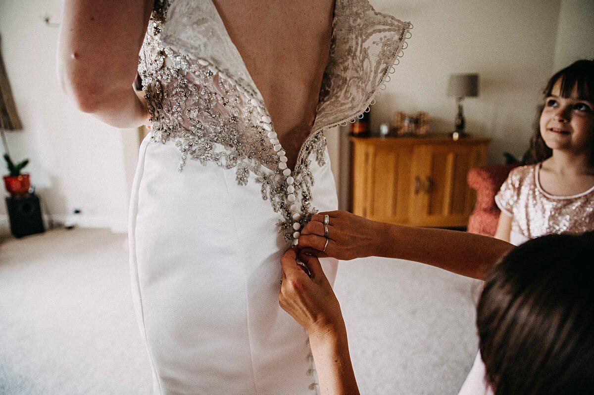 Bride getting into her embellished wedding dress