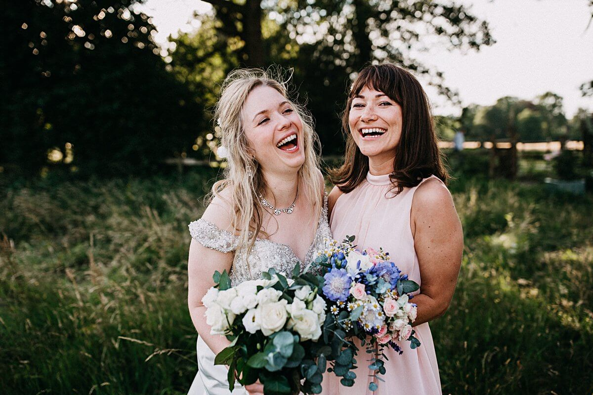 Bride and bridesmaid holding pink, white and purple bouquets