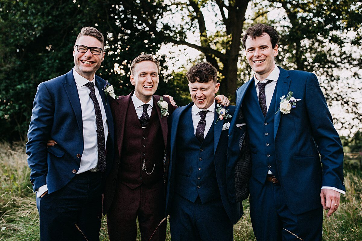 Burgundy Groom's suit and navy ushers suits