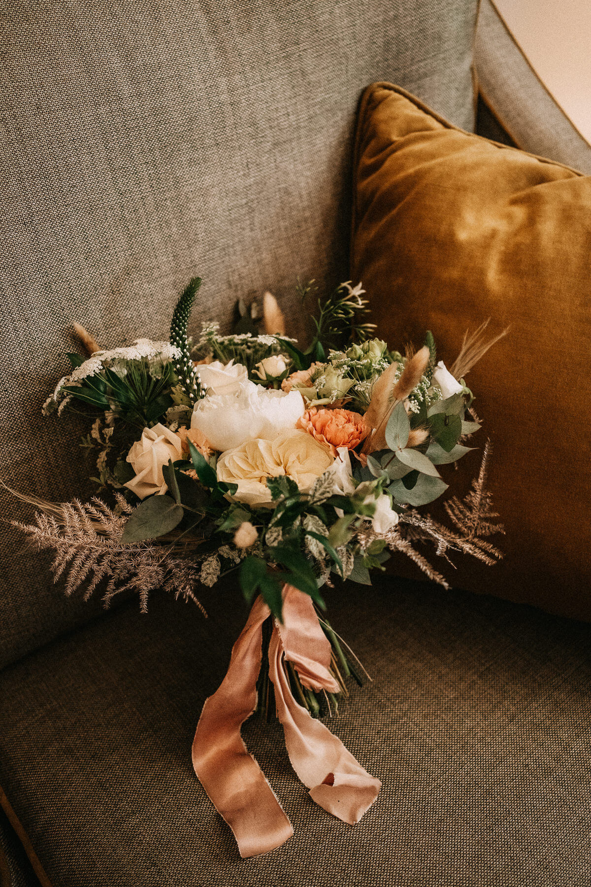 Peach and yellow summer wedding bouquet with pink ribbon