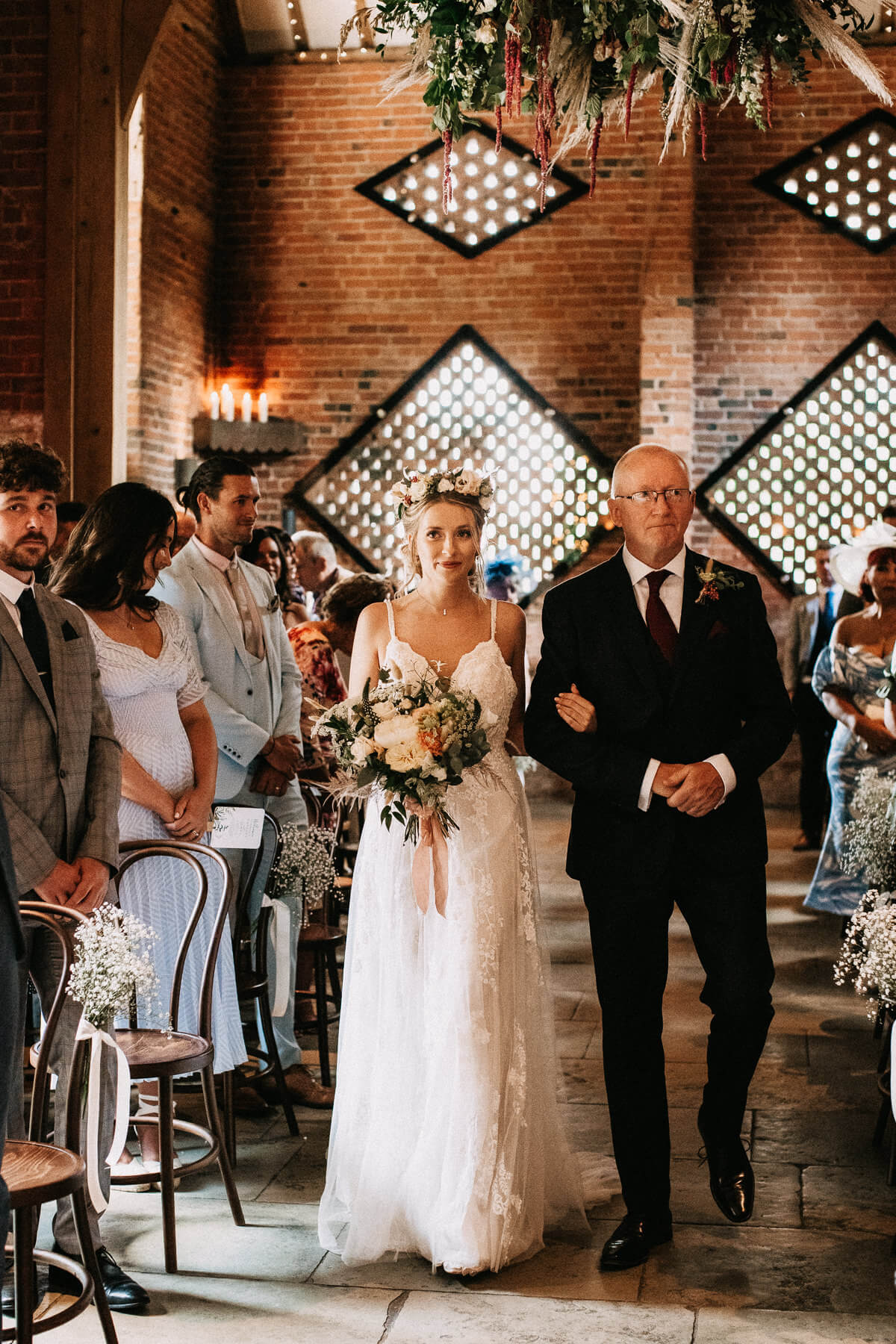 Bride walking down the aisle wearing a flower cronwn