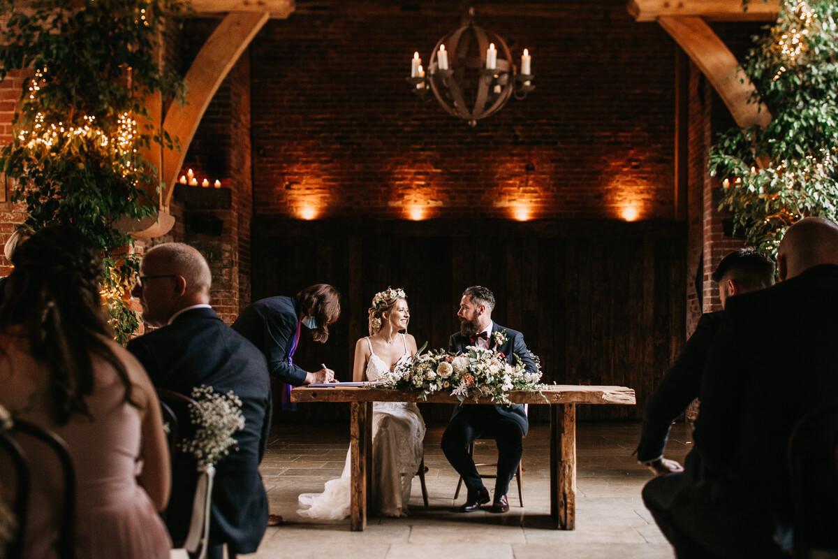 Signing the register at the ceremony Shustoke Barn wedding