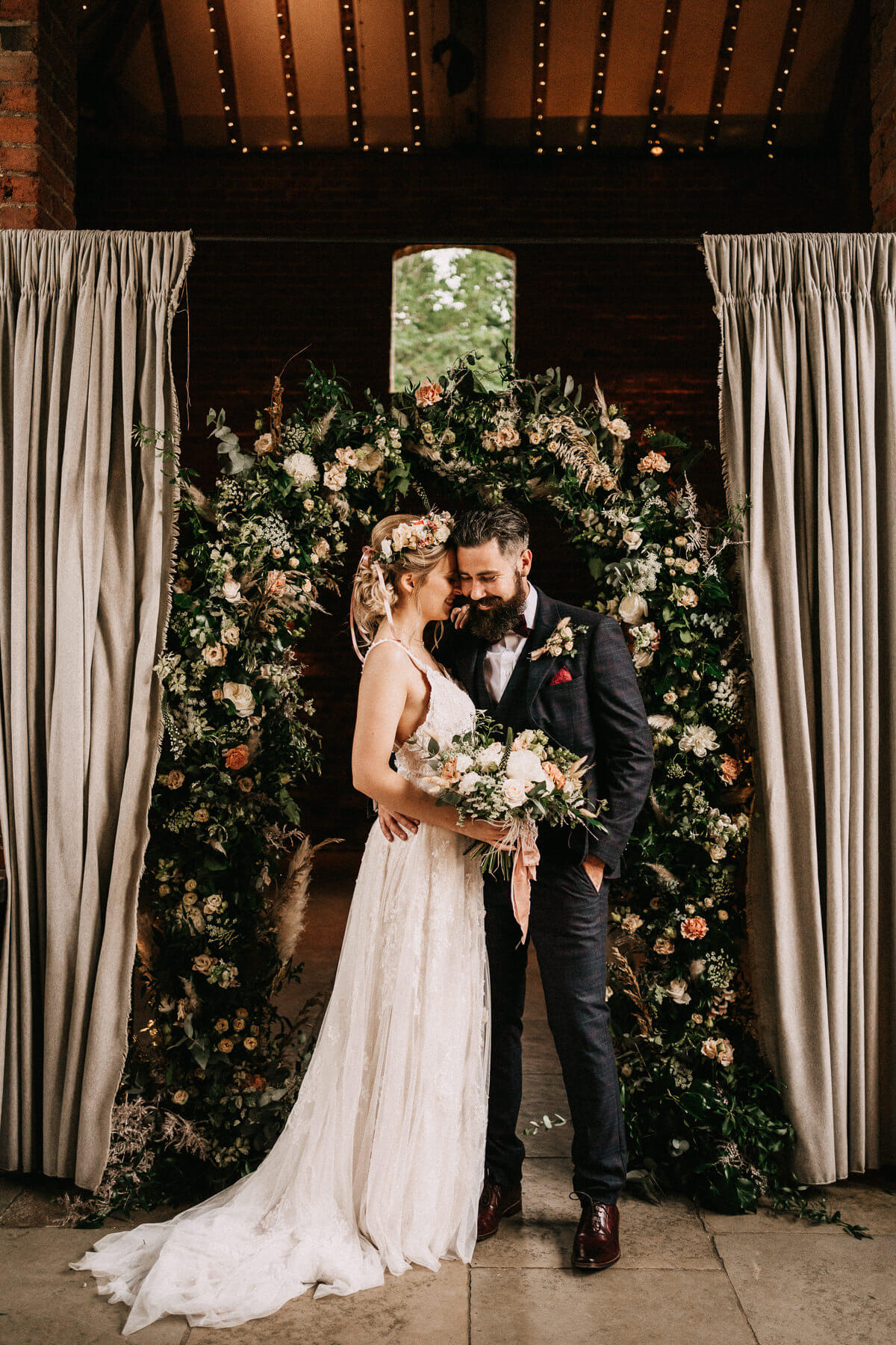 Bride and groom portrait with their flower arch