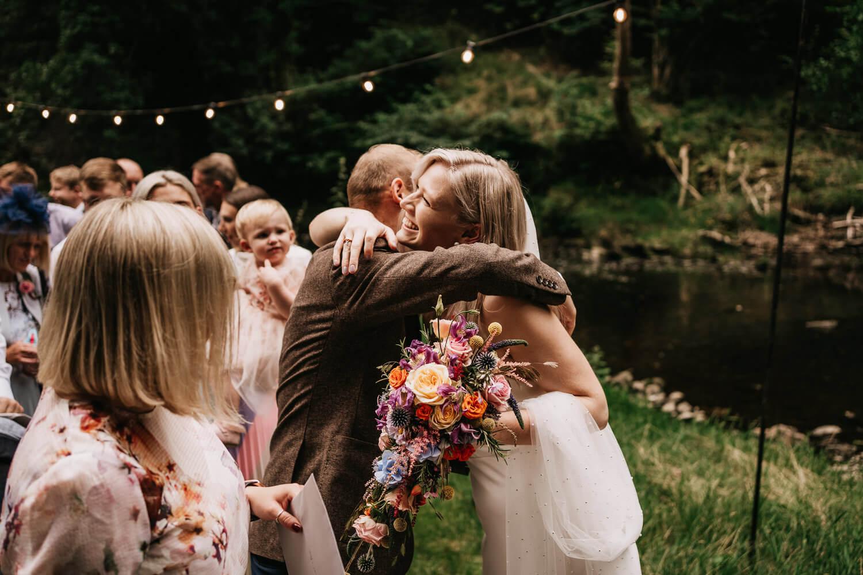 Bride hugging friends at Tipi wedding
